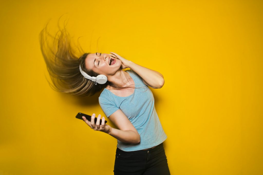 Woman dancing it out with headphones and a smart phone.