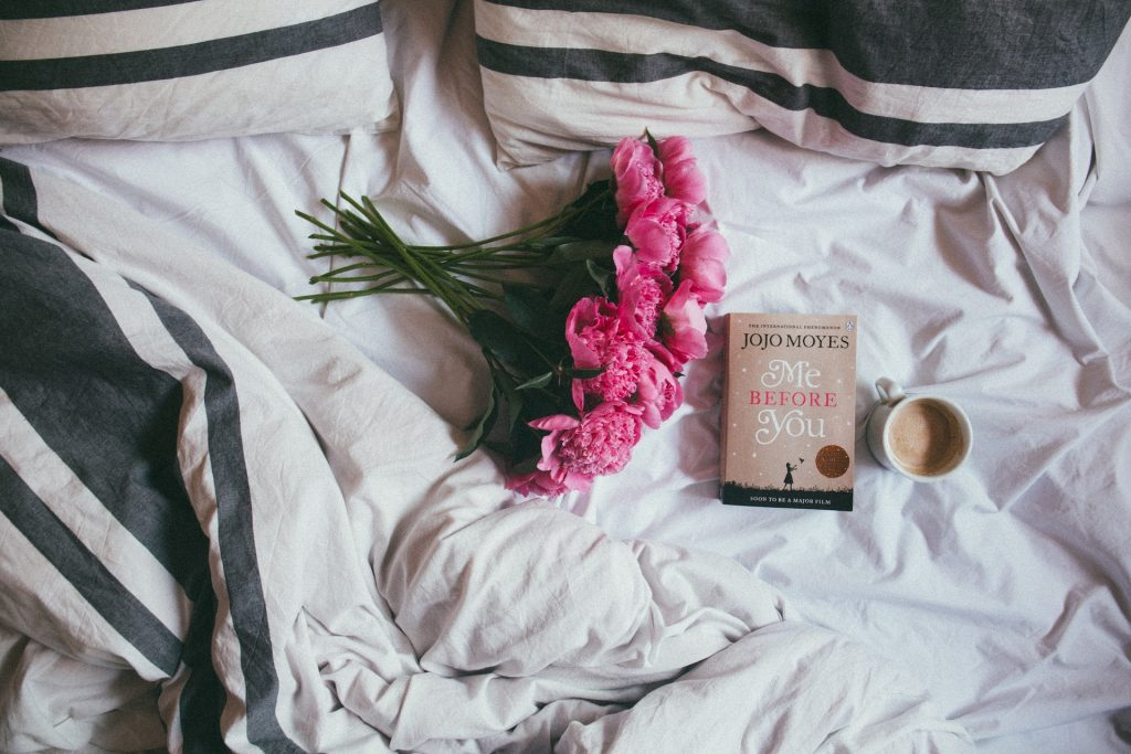 Bed, book, flowers, hot drink. Be kind to yourself. Duvet day.