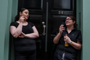 Ladies smoking together outside a door.